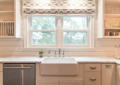 The farm sink and vintage style drawer hardware add a timeless touch to this modern farmhouse kitchen remodeling project in Atlanta
