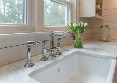 The bridge faucet on the farm sink looks like an antique, but is brand new in the kitchen remodeling project in Atlanta