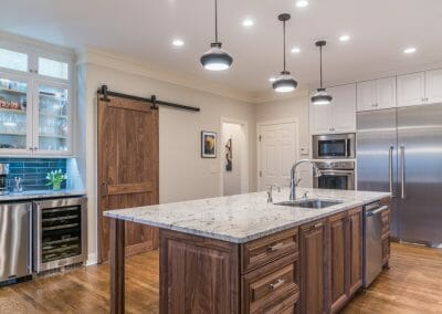 Warm wood island and rustic barn doors in East Cobb kitchen remodeling
