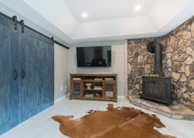 Sitting room with TV and wood stove in Roswell master suite remodel