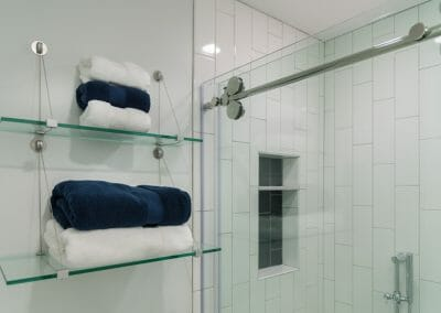 Glass shelving for towels in the Roswell master suite remodeling project