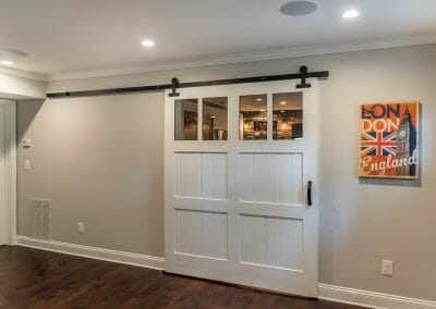 The barn door separates the bar and home theater in entertainment space in East Cobb