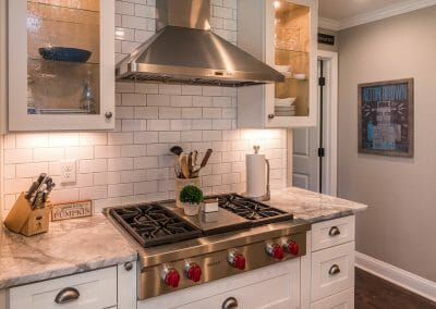 Cooktop and glass-front cabinets in East Cobb kitchen remodel