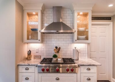 Cooktop, vent hood, cabinetry and subway tile backsplash in East Cobb kitchen remodeling