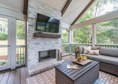 Another view of fireplace, mantel and TV in screened porch remodel in East Cobb