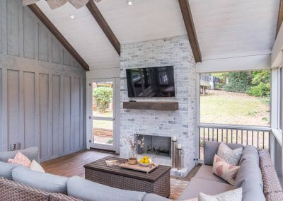 Seating area and fireplace with mantel and TV in screened porch remodel in East Cobb