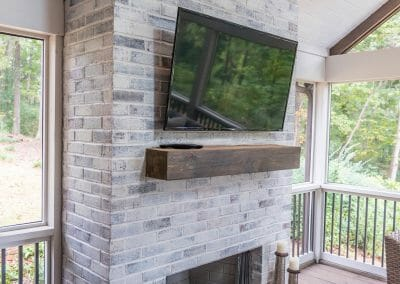 Gas fireplace with mantel and TV in screened porch remodel in East Cobb