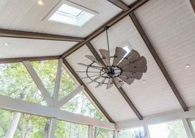 Skylights, ceiling fans, and structural beams in screened porch remodel in East Cobb