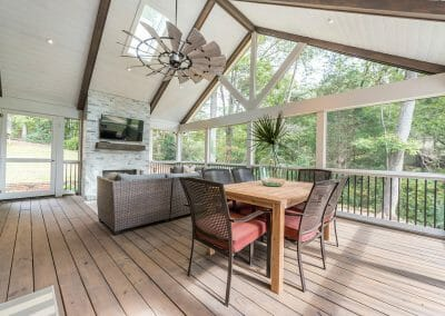 Dining area, seating area and fireplace with TV in screened porch addition in East Cobb