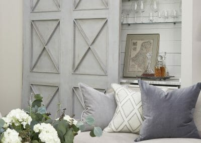 A stylish and practical barn door conceals the dry bar in the Roswell open concept remodel