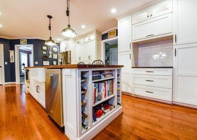Another view of the butcher block island with cabinets and subway tile backsplash