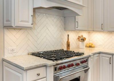 Pro-style range, cabinets, and herringbone tile patterned backsplash in East Cobb