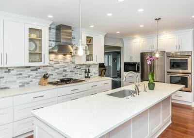 Island, ovens and cooktop view in white kitchen remodel in Sandy Springs
