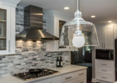 View of light fixture and cooktop with tile backsplash in open kitchen remodel is Sandy Springs