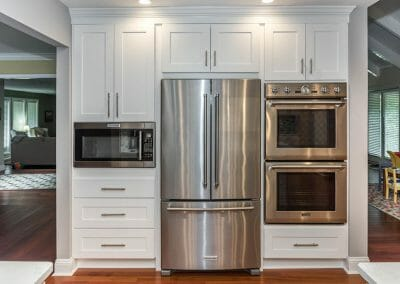 Double ovens and built-in microwave flanking French door fridge in kitchen remodel in Sandy Springs