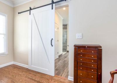 ADA-compliant master bath renovation with barn door access, and wood-look tile floor.
