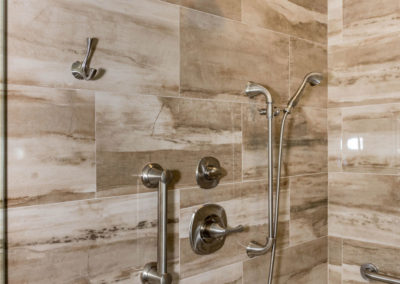 ADA-compliant master bath detail of shower tile (12x24), grab bars, and hand-held shower sprayer.