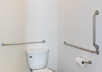 """ADA master bath renovation with wood-look tile floor, water closet with 5-foot clearance for a wheelchair, grab bars, and comfort-height toilet (2 1/2"""" higher seat level)."""