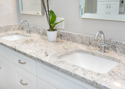 Bathroom double-sink vanity with chrome faucet fixtures and granite countertop.