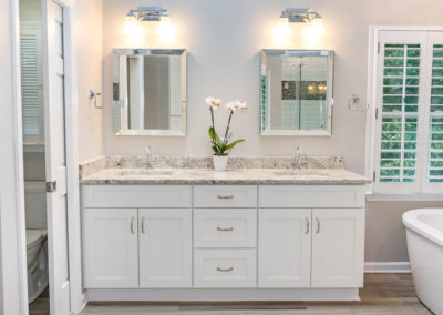 Master bath renovation has white Milan-style double vanity with granite top, three center drawers and double-doors below each sink, chrome fixtures, bevel-framed mirrors, and chrome wall fixtures.