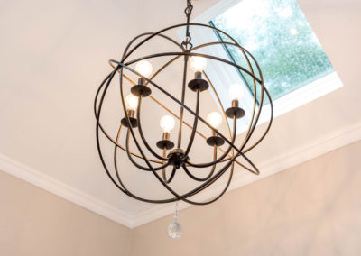 Six-bulb pendant light, with metal-hooped sphere and antique copper finish.