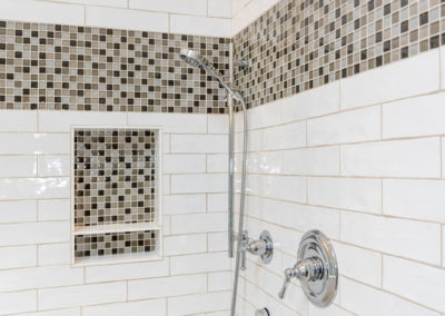 """Shower with wavy white subway tile (2.5""""x8"""") and 12"""" glass mosaic band."""